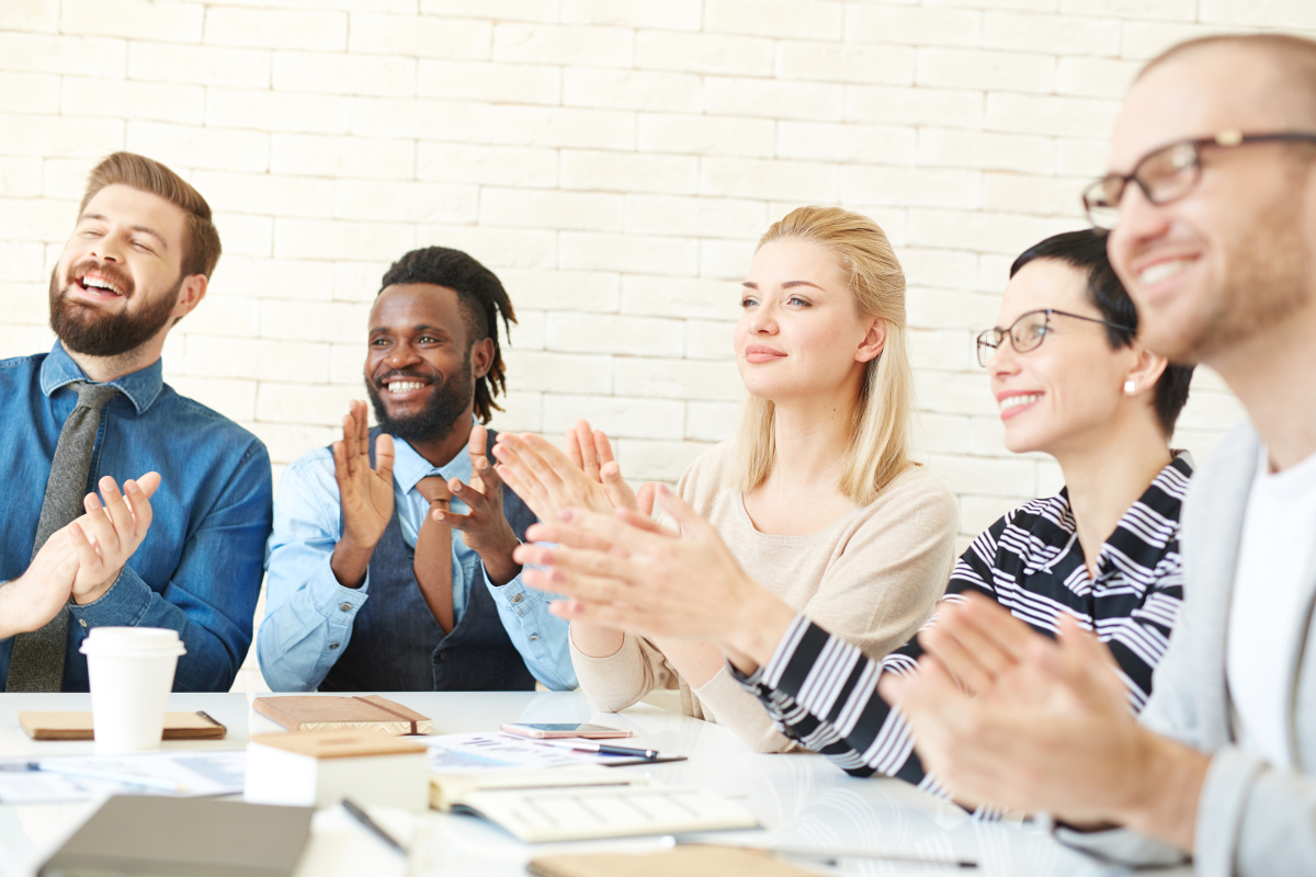 Business Team Seated Around Meeting Table Smiling and Applauding