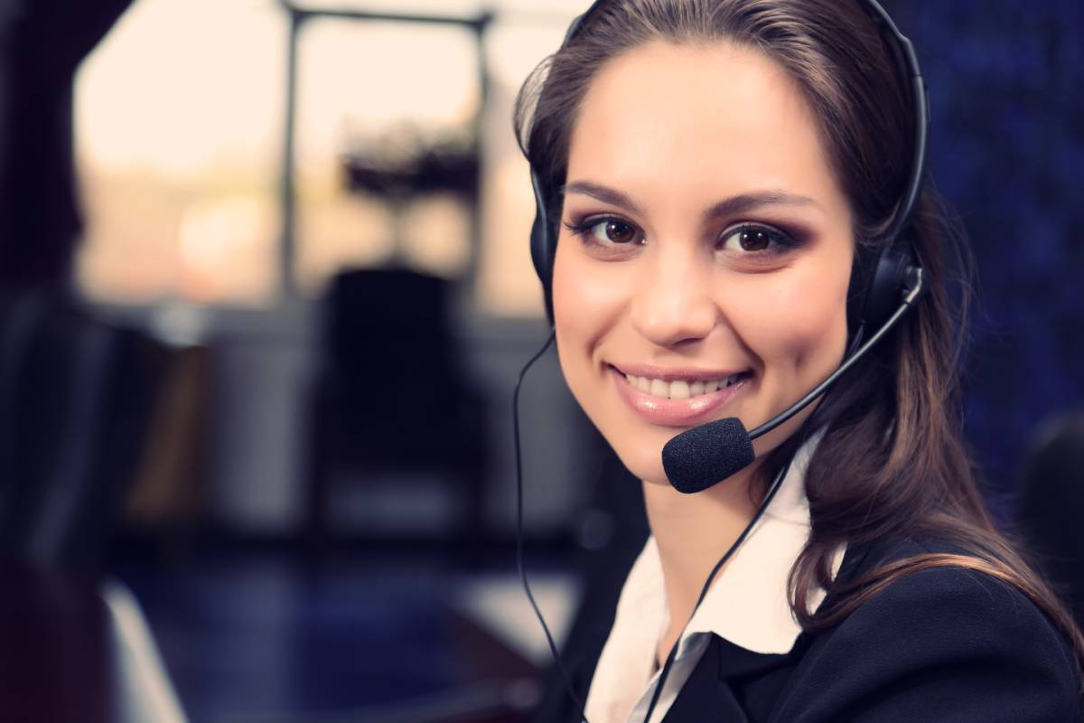 Female Call Center employee smiling at work while wearing a headset