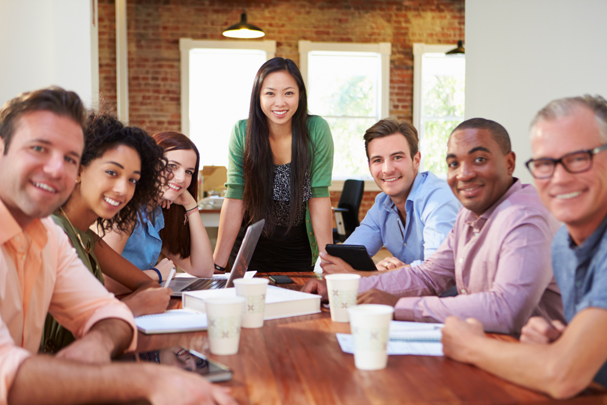 Woman standing over conference table with employees on either side