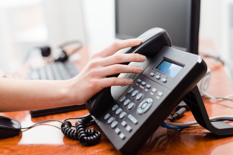 Close Up of Hand On VoIP Desk Phone