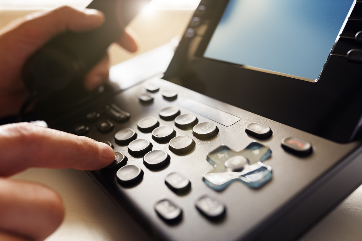 Close Up of Hand Dialing VoIP Phone