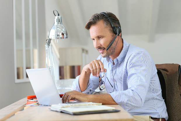 Man in blue shirt on a laptop with a headset on working from home.