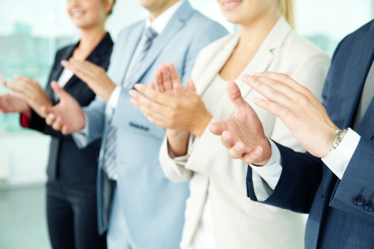 Two businessmen and two businewomen clapping in celebration