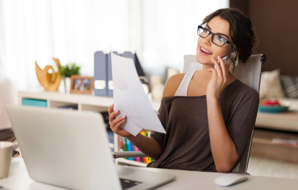 Woman on Phone Seated in Front of Computer in Home Office