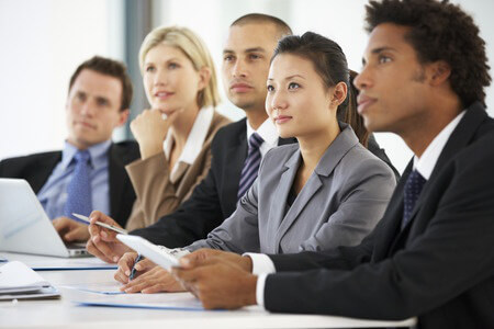 A row of diverse workers in business attire sitting on the side of a table, all of them looking in the same direction