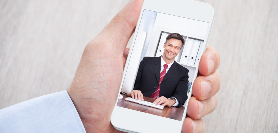 A man holding a smartphone in one hand, the screen showing someone he is video conferencing with