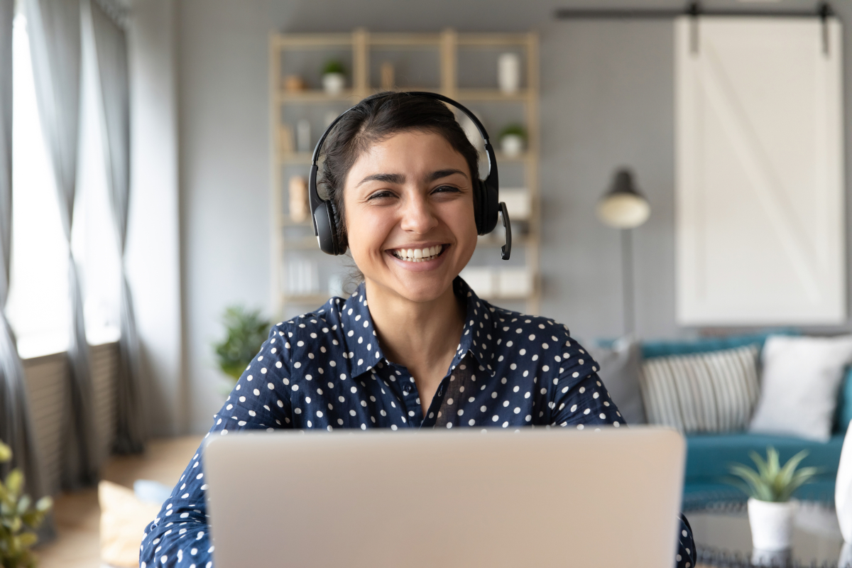 Smiling Woman Wearing Headset Seated in Front of Laptop at Home