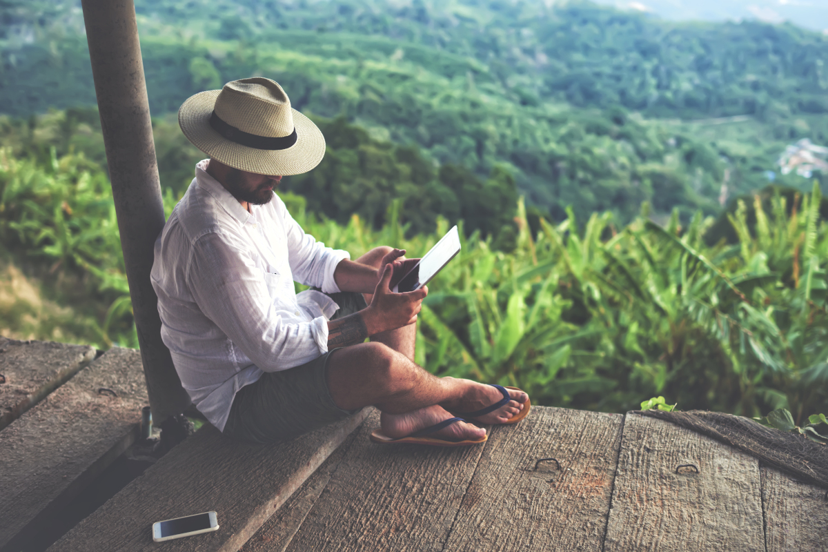 Man on Deck in Secluded Green Hillside Using Tablet